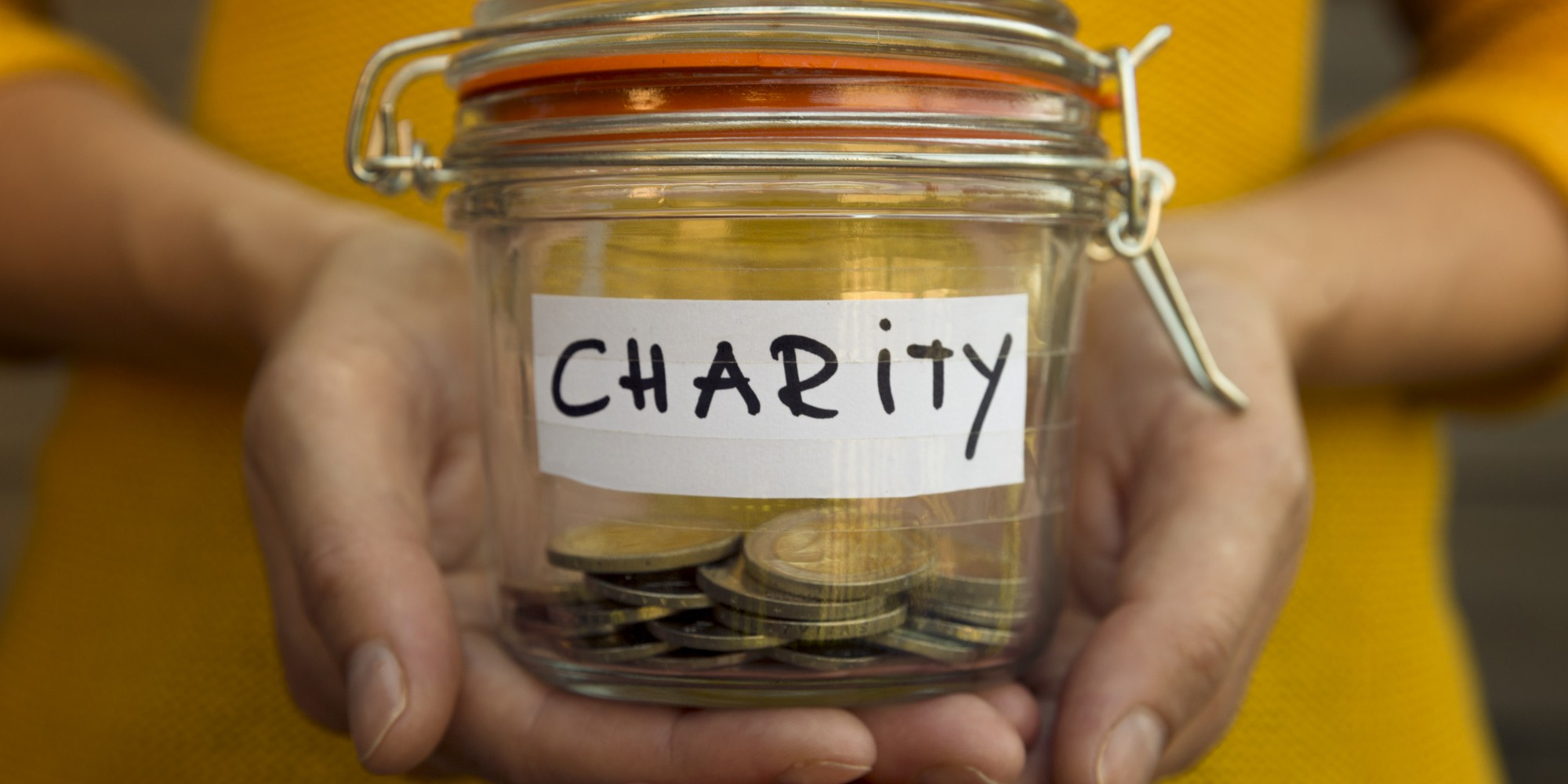 Woman collecting money for charity and holds jar with coins.