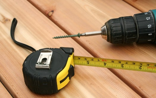 A drill and a tape measure on a new deck.