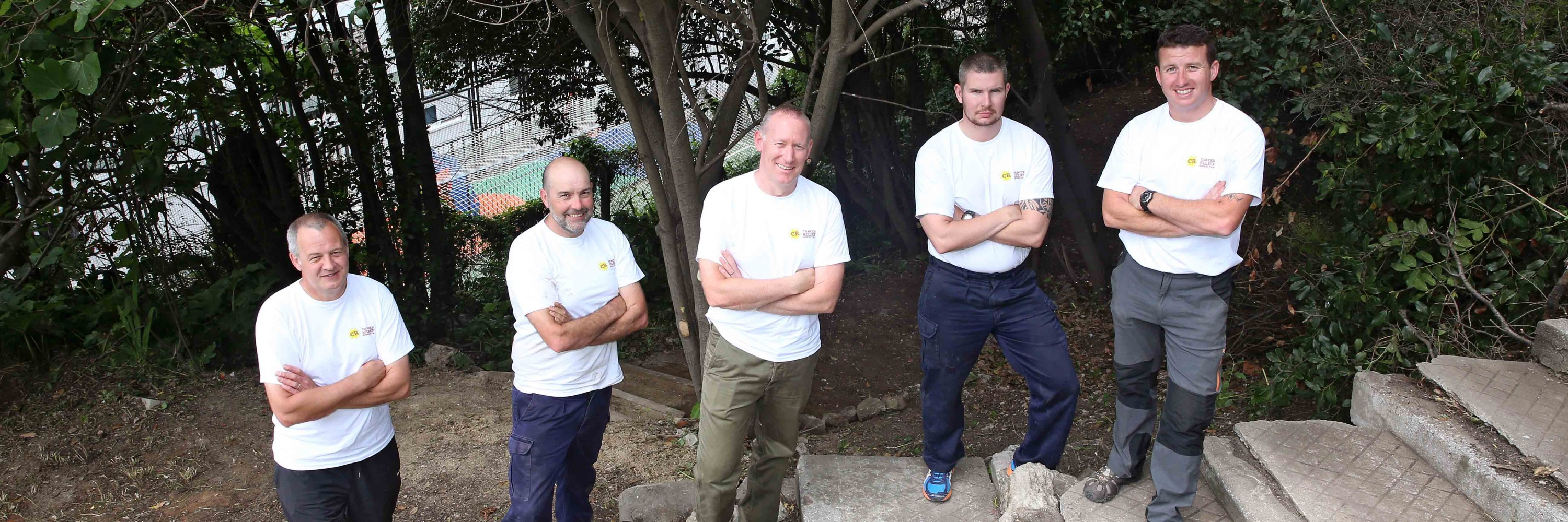 Staff from HQ British Forces Gibraltar volunteer to help out clearing an overgrown garden at the Cancer Relief House.